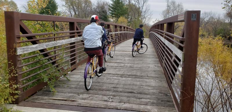 CIEP students riding bikes across a bridge